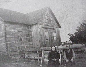 unidentified couple in front of log cabin