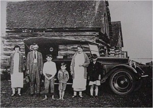 unidentified family standing outside a car