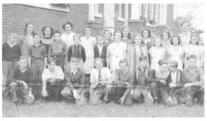 Class photo of Killaloe Public School 1943. Betty Mullin Collection. Front row, left to right, Ken Okum, Ronald Lisk, Allan Wallbridge, Garnet Kosmack, Clifford Okum, Willard Gienow, Gilbert Hein, Delmer Brose, and Howard Felhaber; middle row, left to right, Kenneth Brose, Everett Gienow, Walter Bloedow, Herman Bloedow, Marjorie Burke, Phyllis Noack, Dorothy Lisk, Grace Chatsick, Fern Chatsick and Marilyn Moore; back row, left to right, Violet Okum, Phyllis Tullis, Evelyn Stevenson, principal; Anna Noack, Audrey Okum, Lois Wilkie, Betty Kuehl, Annabelle Schroeder, Irwin Risto