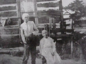 unidentified couple in front of log house